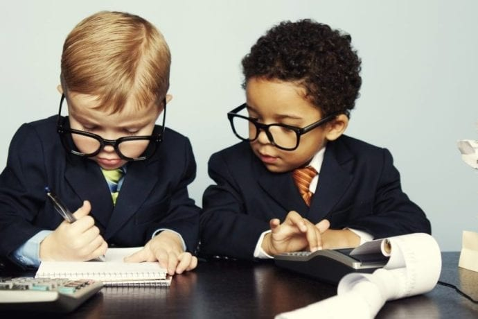 children in professional clothing looking at financial documents